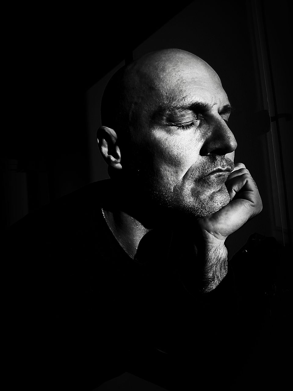 one person, headshot, beard, indoors, males, portrait, mature men, lifestyles, mid adult men, men, real people, facial hair, adult, mid adult, looking away, looking, leisure activity, completely bald, mature adult, contemplation, dark, hair loss, black background