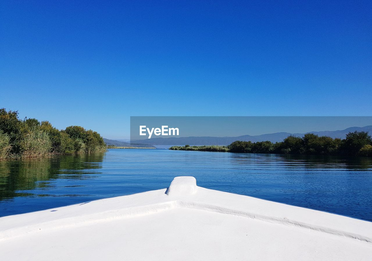 water, sky, blue, copy space, beauty in nature, tree, scenics - nature, clear sky, nature, tranquil scene, tranquility, plant, lake, day, non-urban scene, no people, white color, idyllic, outdoors