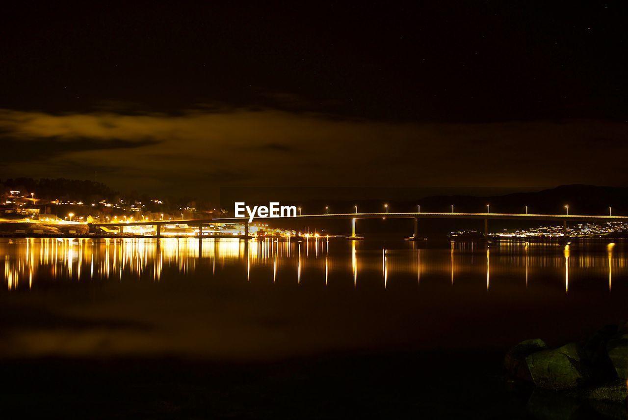 REFLECTION OF ILLUMINATED SKY OVER SEA AT NIGHT