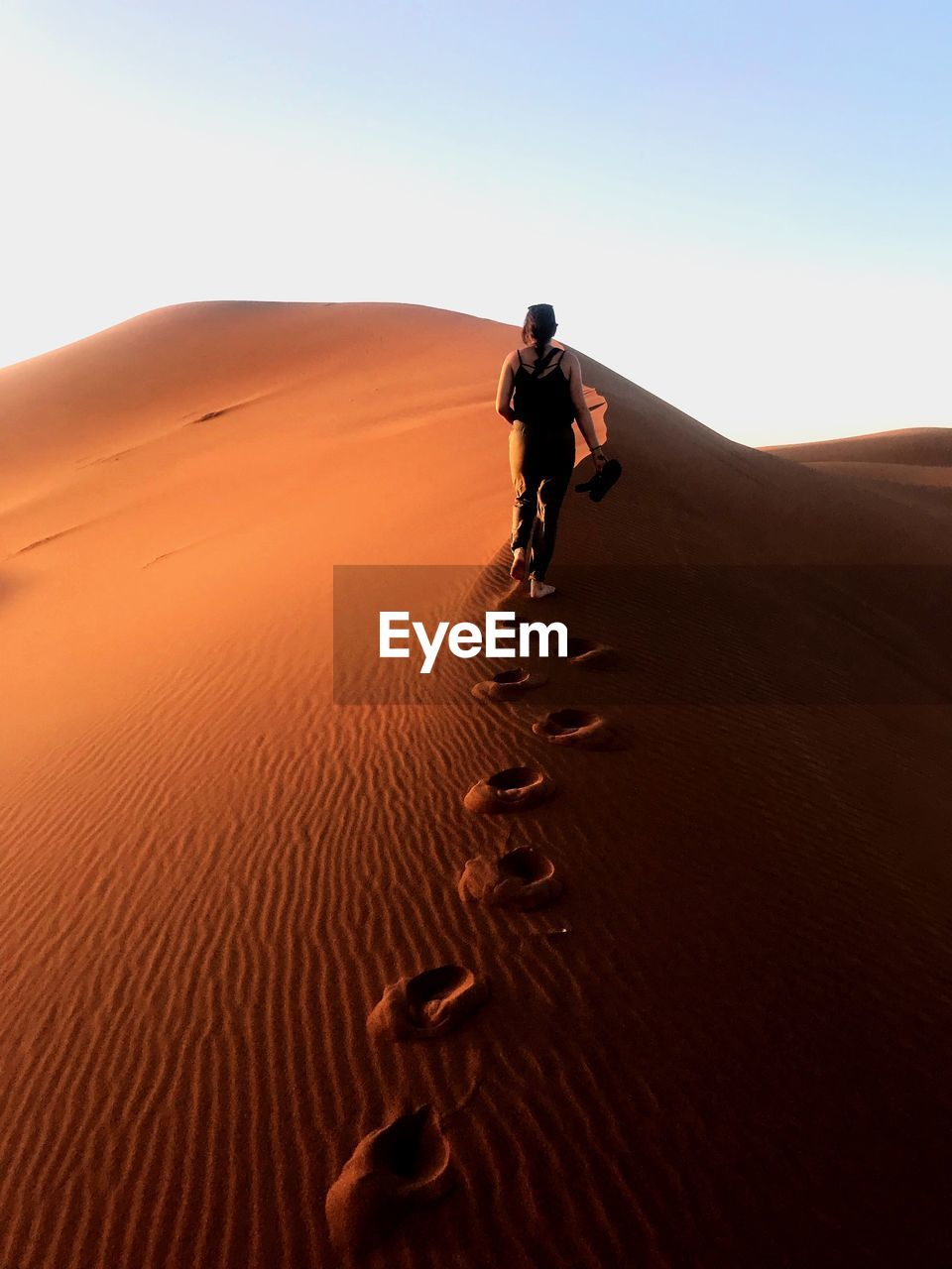 desert, landscape, land, sand dune, sand, one person, arid climate, climate, scenics - nature, sky, nature, environment, full length, walking, men, remote, beauty in nature, day, tranquil scene, non-urban scene, outdoors