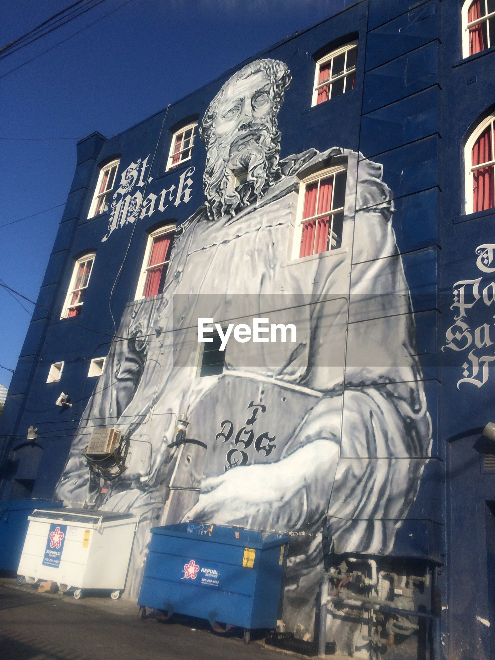 building exterior, architecture, built structure, low angle view, graffiti, text, western script, building, art, human representation, communication, art and craft, city, window, creativity, day, sky, wall - building feature, outdoors