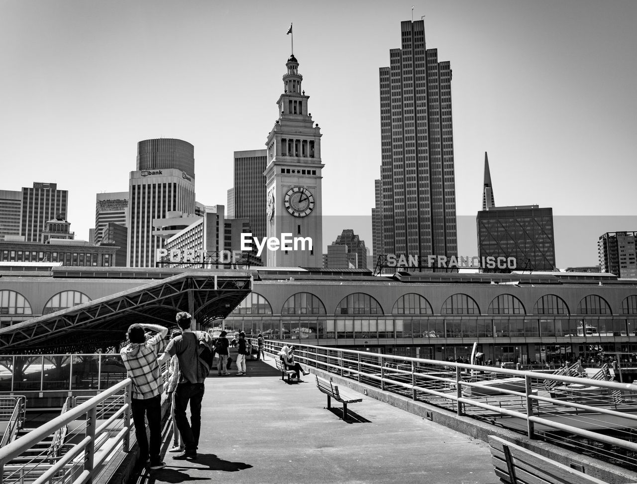 architecture, built structure, building exterior, real people, city, skyscraper, railing, large group of people, walking, tower, men, clear sky, women, travel, outdoors, lifestyles, city life, day, travel destinations, bridge - man made structure, sky, modern, people, adult