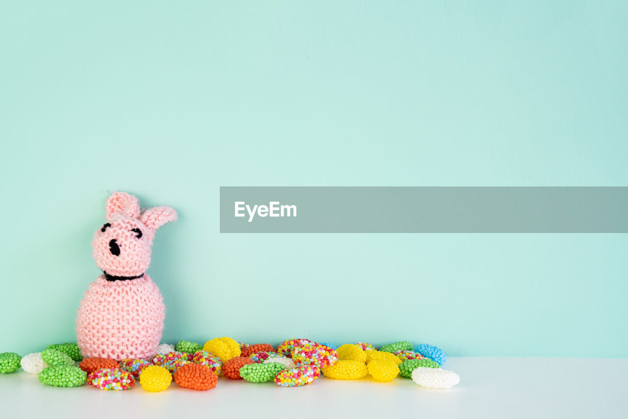 copy space, studio shot, still life, animal representation, indoors, representation, colored background, stuffed toy, food, no people, toy, food and drink, animal, table, mammal, sweet food, sweet, creativity, animal themes, freshness, temptation, blue background