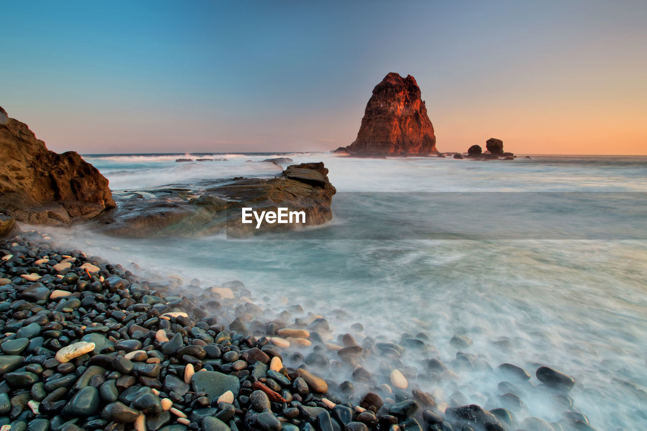 rock, solid, rock - object, sea, water, beauty in nature, scenics - nature, land, sky, motion, beach, wave, nature, rock formation, tranquil scene, tranquility, non-urban scene, no people, idyllic, horizon over water, outdoors, pebble, stack rock, power in nature, rocky coastline