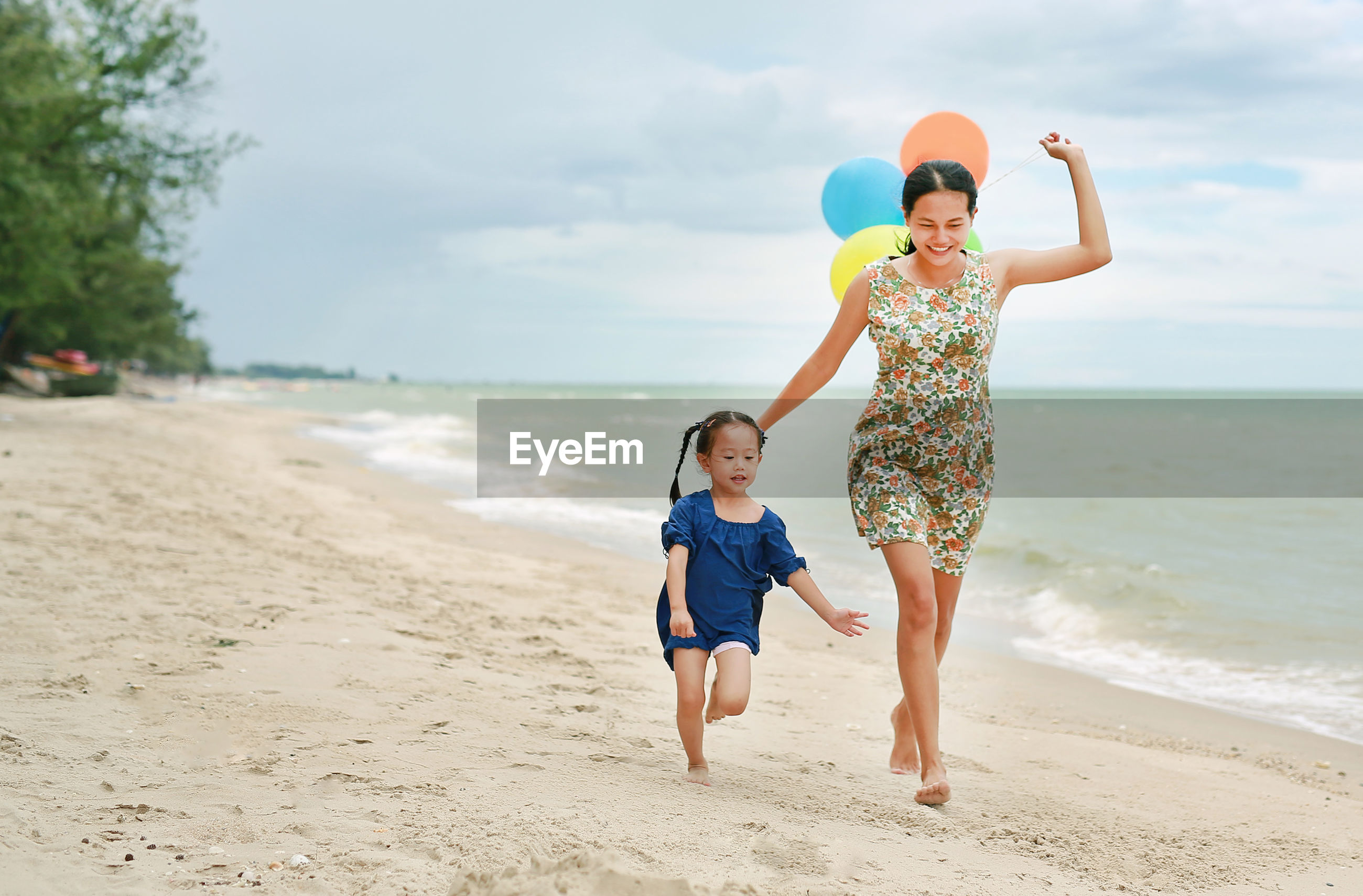 Cheerful mother and daughter running at beach against sky