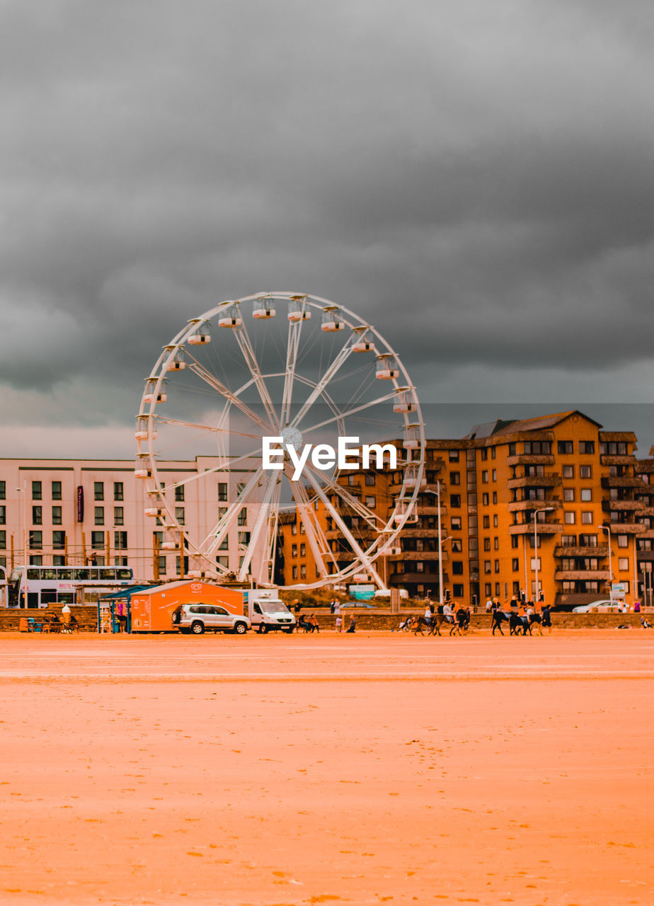 Ferris Wheel In Amusement Park Against Cloudy Sky