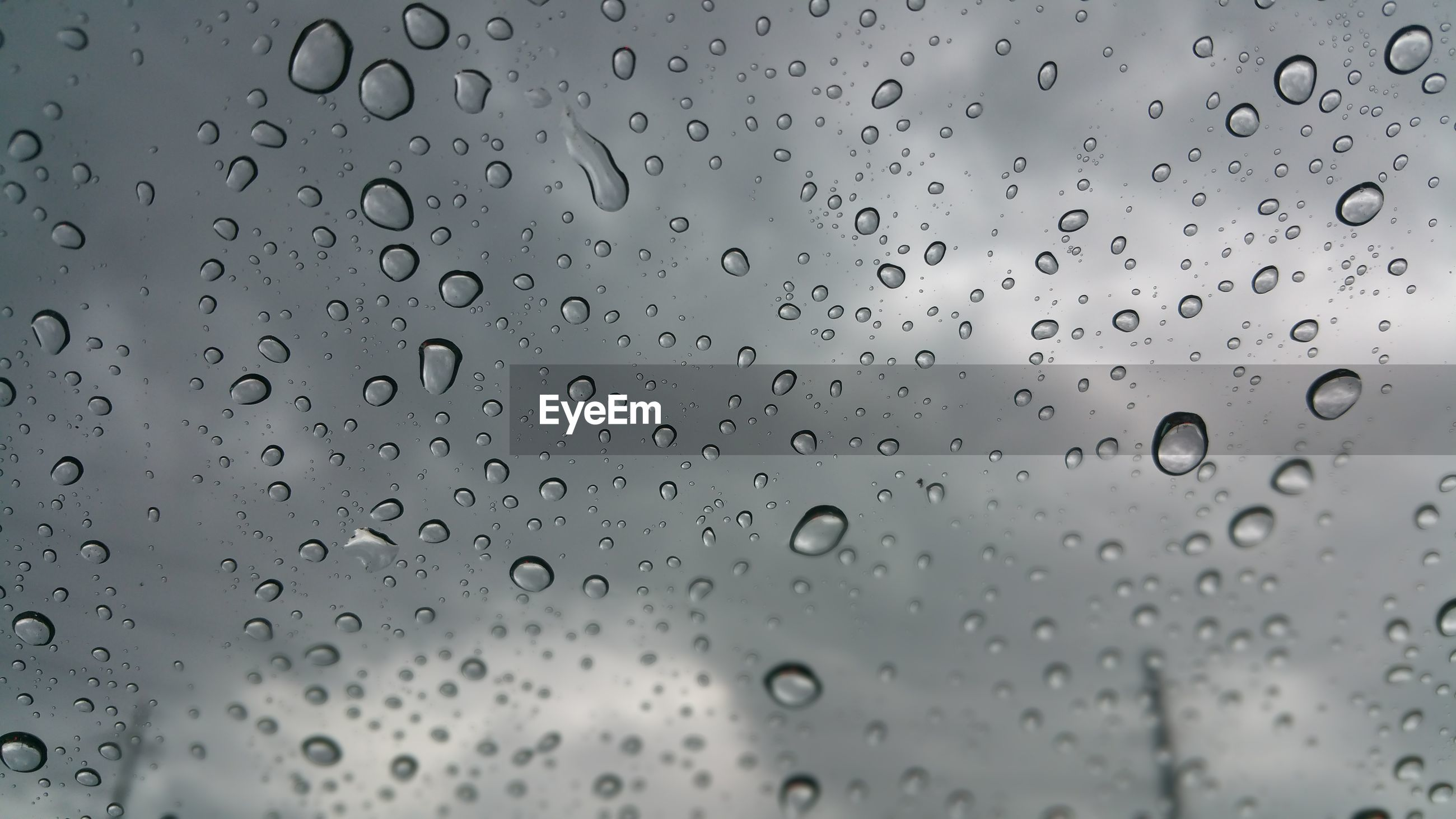 CLOSE-UP OF WATER DROPS ON GLASS AGAINST BLURRED BACKGROUND