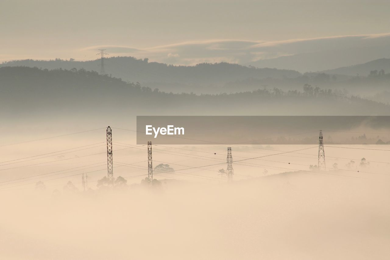 Electricity Pylons Against Mountains In Foggy Weather
