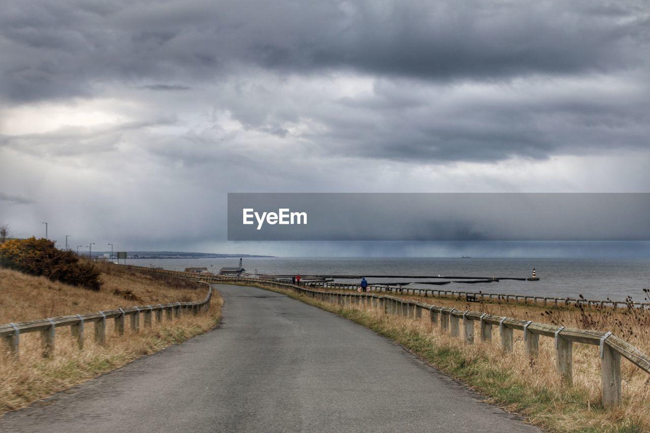 cloud - sky, sky, direction, water, the way forward, scenics - nature, nature, sea, beauty in nature, tranquil scene, tranquility, road, overcast, no people, transportation, horizon, day, outdoors, horizon over water, diminishing perspective, long