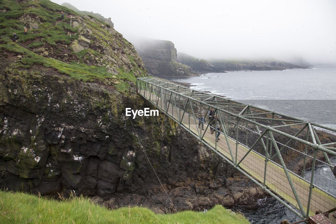 water, fog, nature, mountain, day, scenics - nature, beauty in nature, rock, tranquil scene, tranquility, solid, rock - object, bridge, bridge - man made structure, non-urban scene, connection, built structure, architecture, outdoors, no people