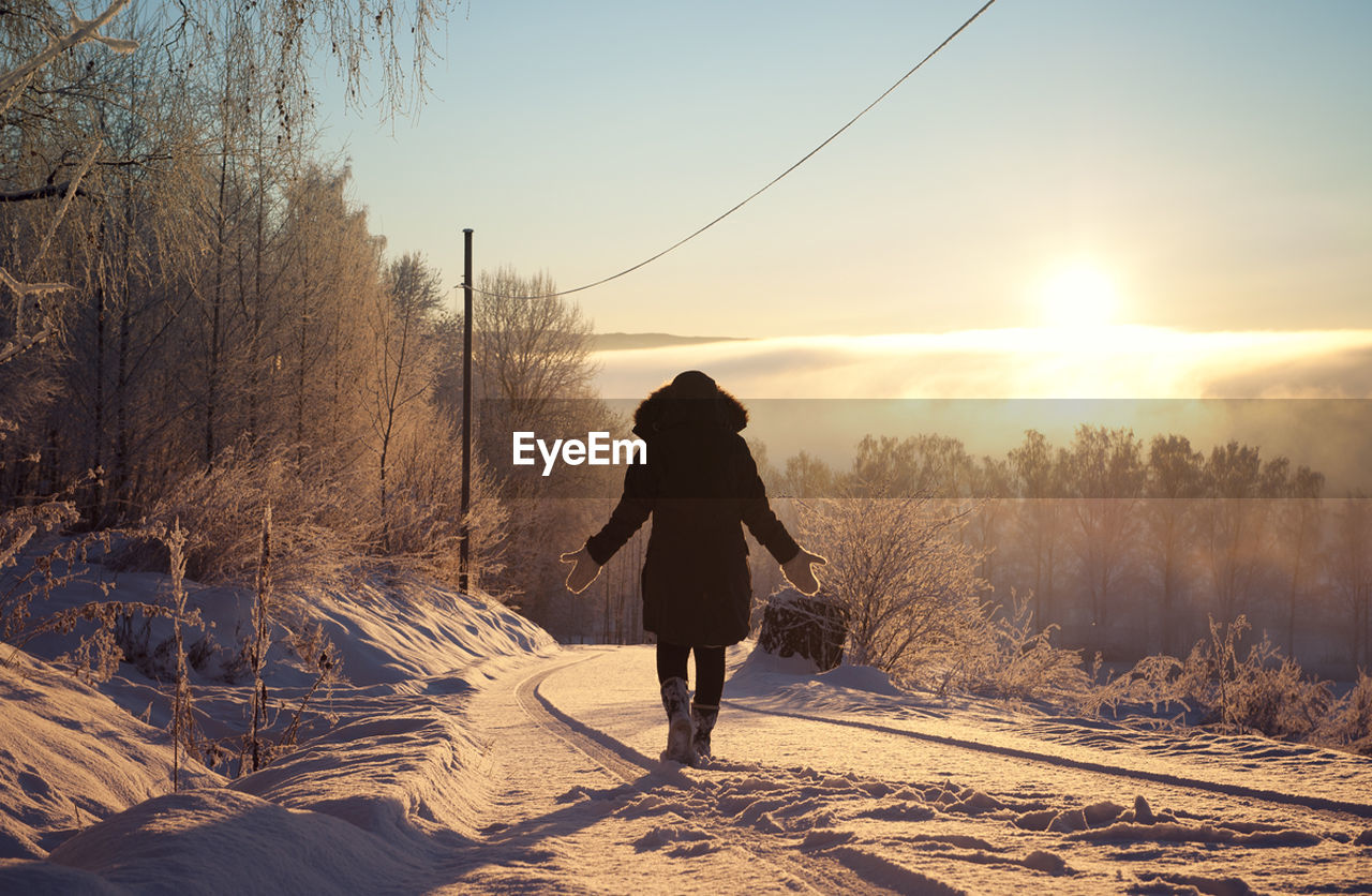 winter, snow, cold temperature, nature, sunset, rear view, sun, one person, tree, field, full length, beauty in nature, bare tree, silhouette, sunlight, real people, outdoors, sky, landscape, standing, day, warm clothing, people