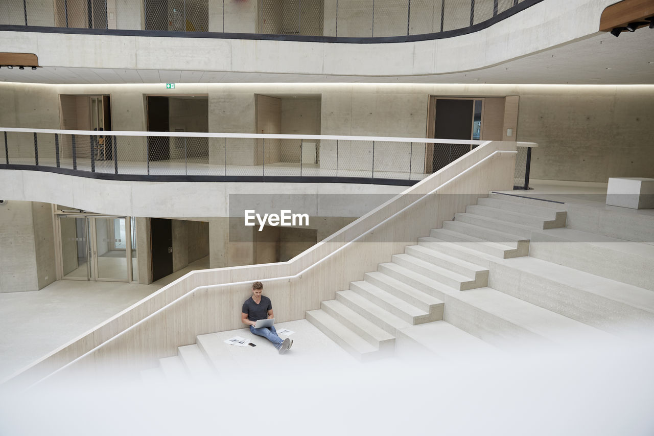 MAN SITTING ON STAIRCASE IN BUILDING