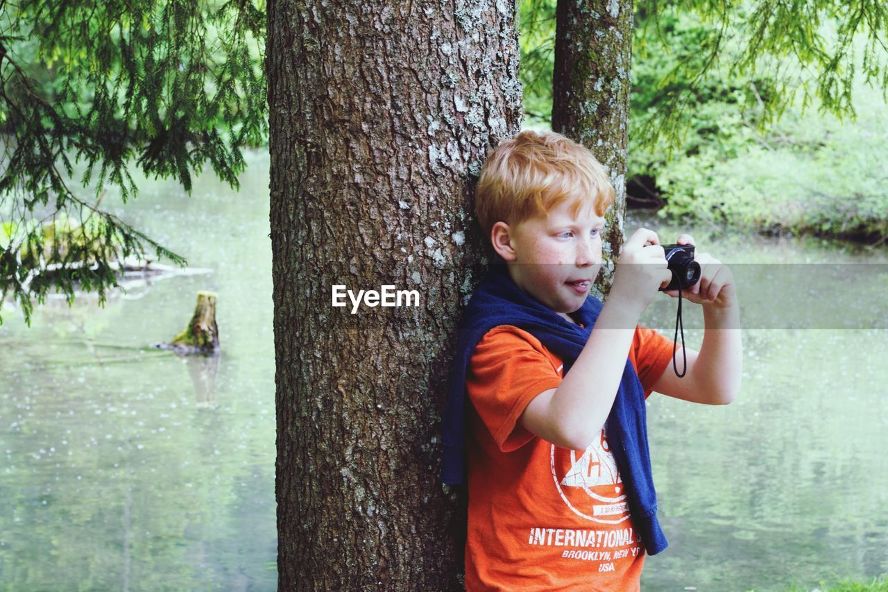 childhood, holding, tree, tree trunk, leisure activity, one person, boys, males, one boy only, day, outdoors, playing, water, nature, people, camera - photographic equipment, child, children only, animal themes, adult