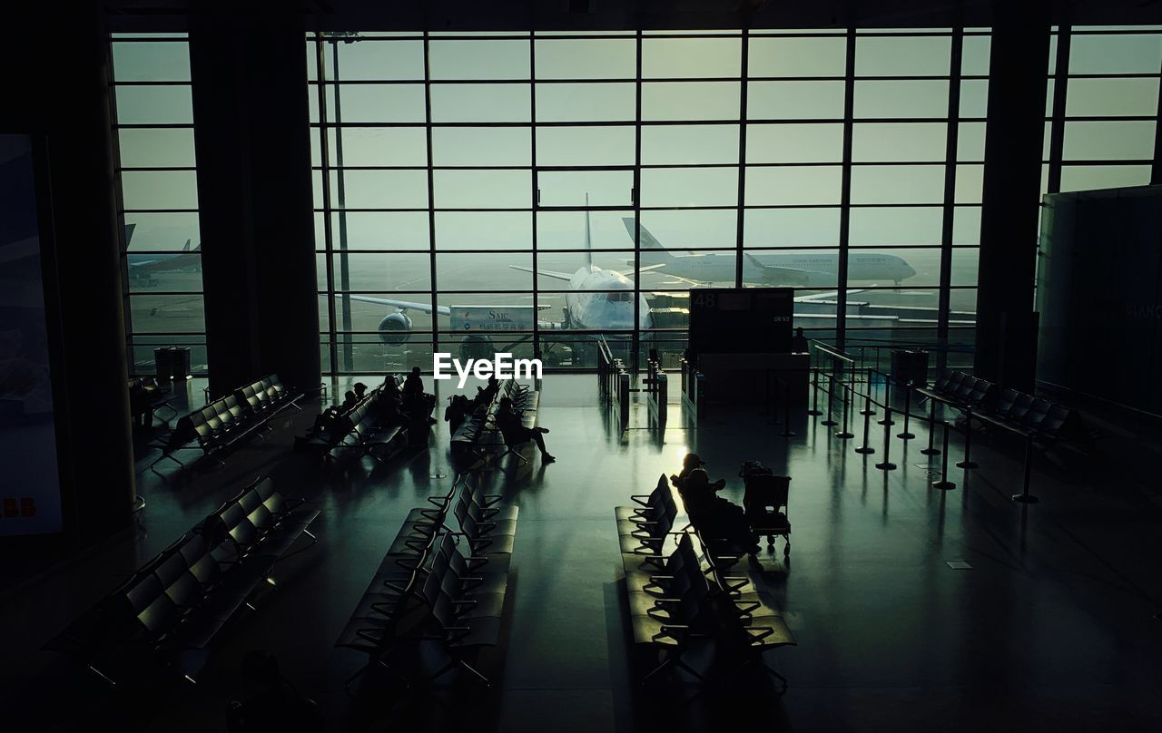 window, architecture, indoors, glass - material, airport, built structure, transportation, travel, real people, group of people, flooring, crowd, day, in a row, transparent, building, modern, lifestyles, large group of people, airport departure area, airport terminal