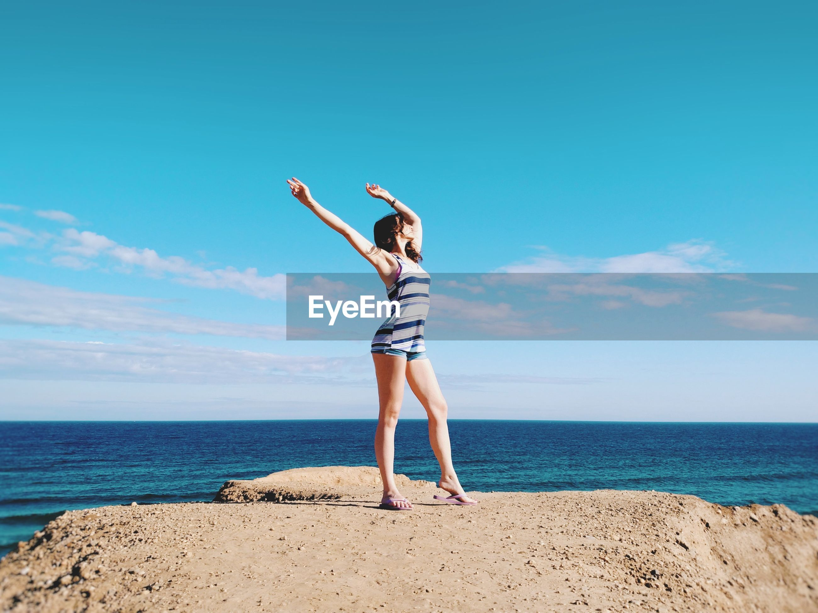 Young woman with arms raised standing at beach against sky during sunny day