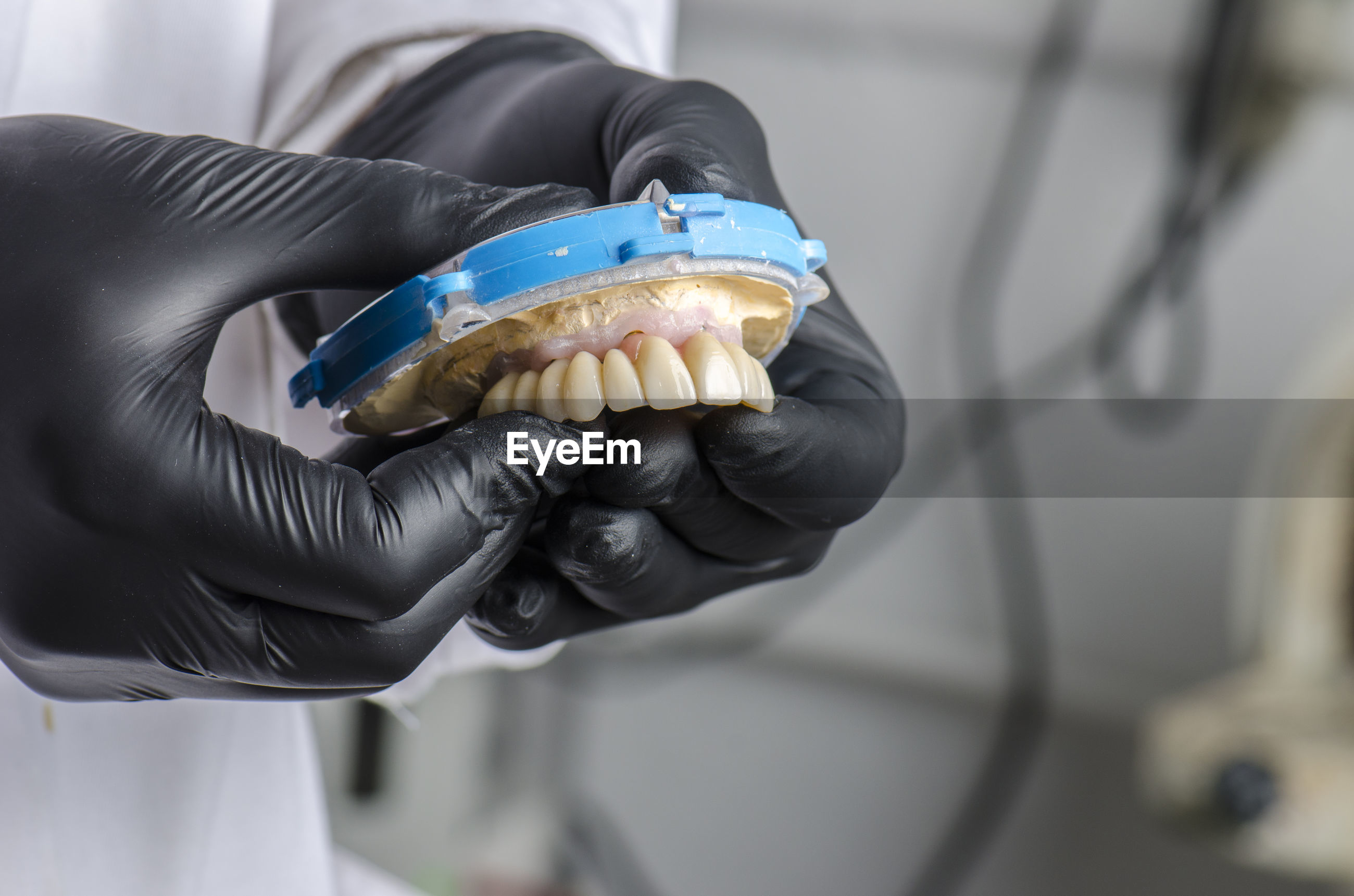 Midsection of dentist working on dentures at clinic