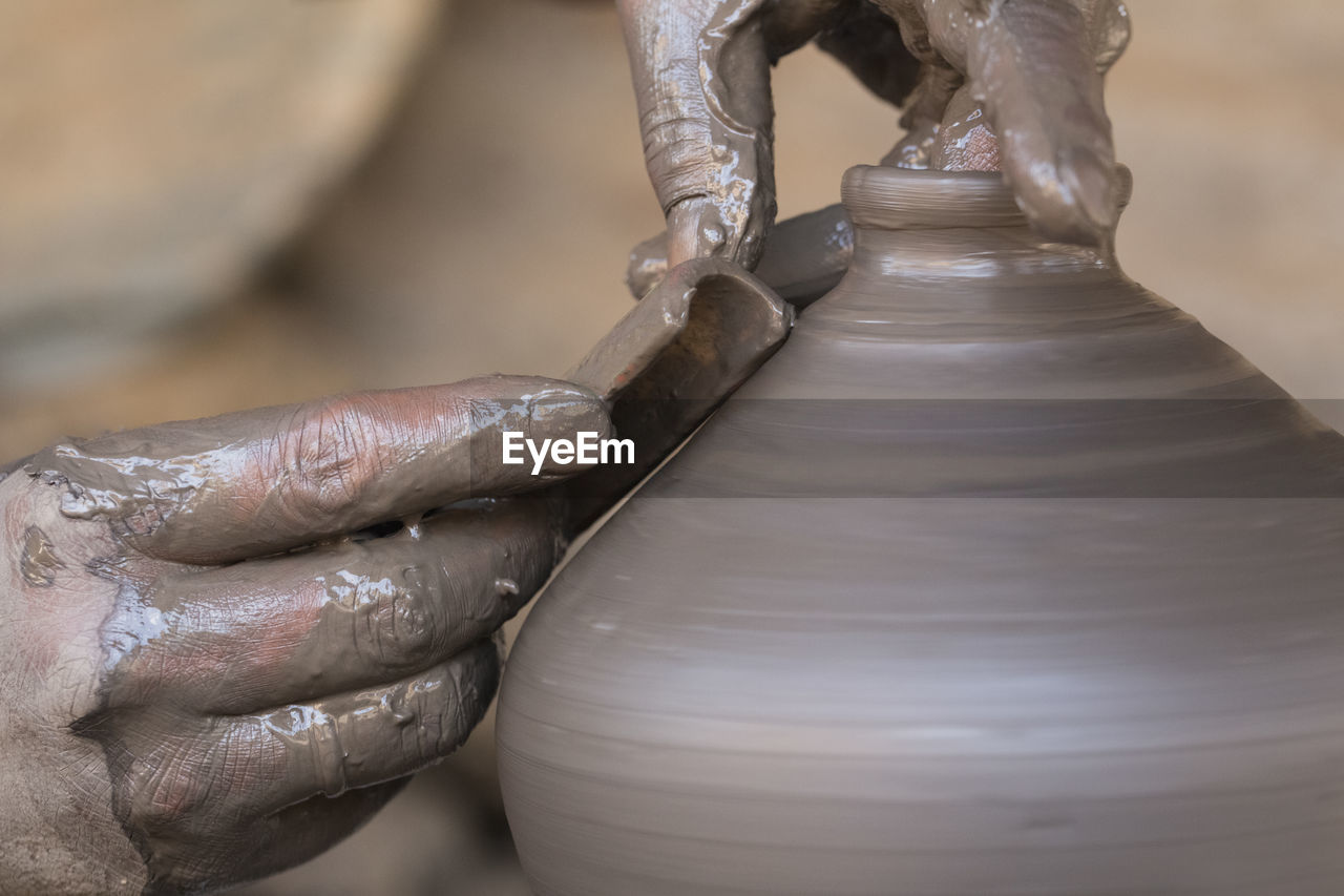 human hand, hand, human body part, art and craft, working, pottery, occupation, craft, spinning, creativity, close-up, skill, focus on foreground, indoors, clay, real people, expertise, motion, body part, craftsperson, finger
