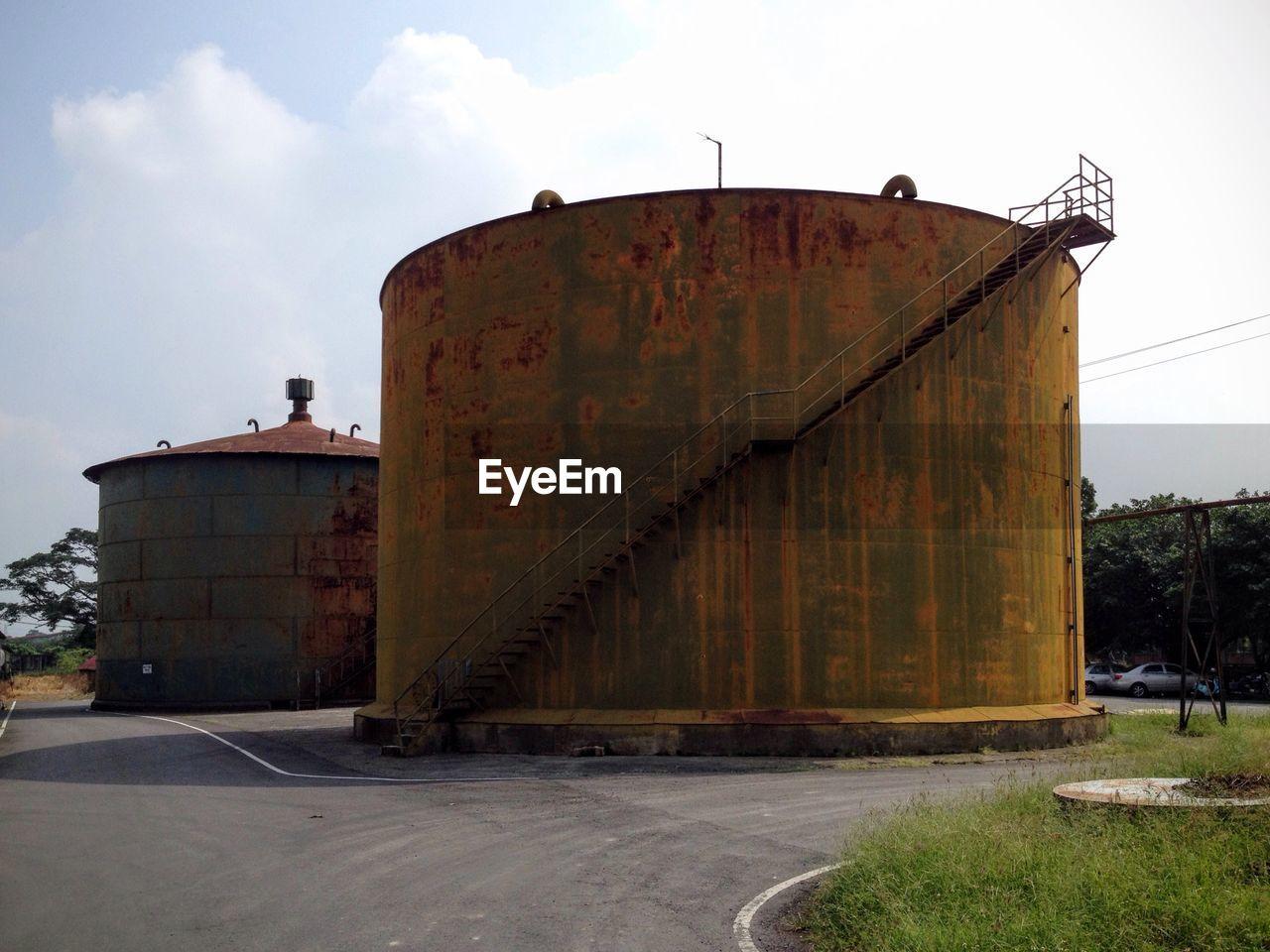 Abandoned rusty silos against sky