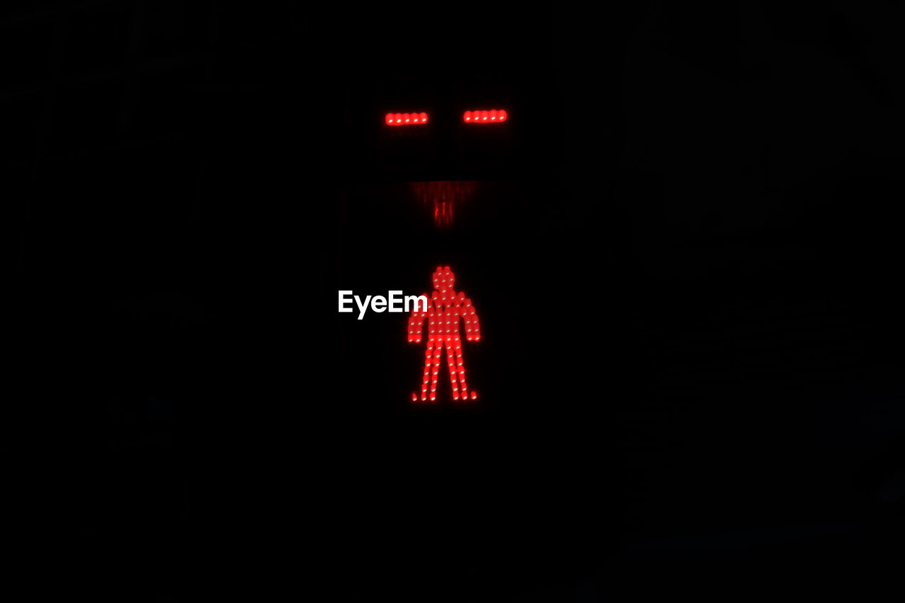 illuminated, red, sign, lighting equipment, no people, dark, light, guidance, indoors, communication, close-up, night, copy space, red light, transportation, stoplight, direction, glowing, representation, human representation, black background