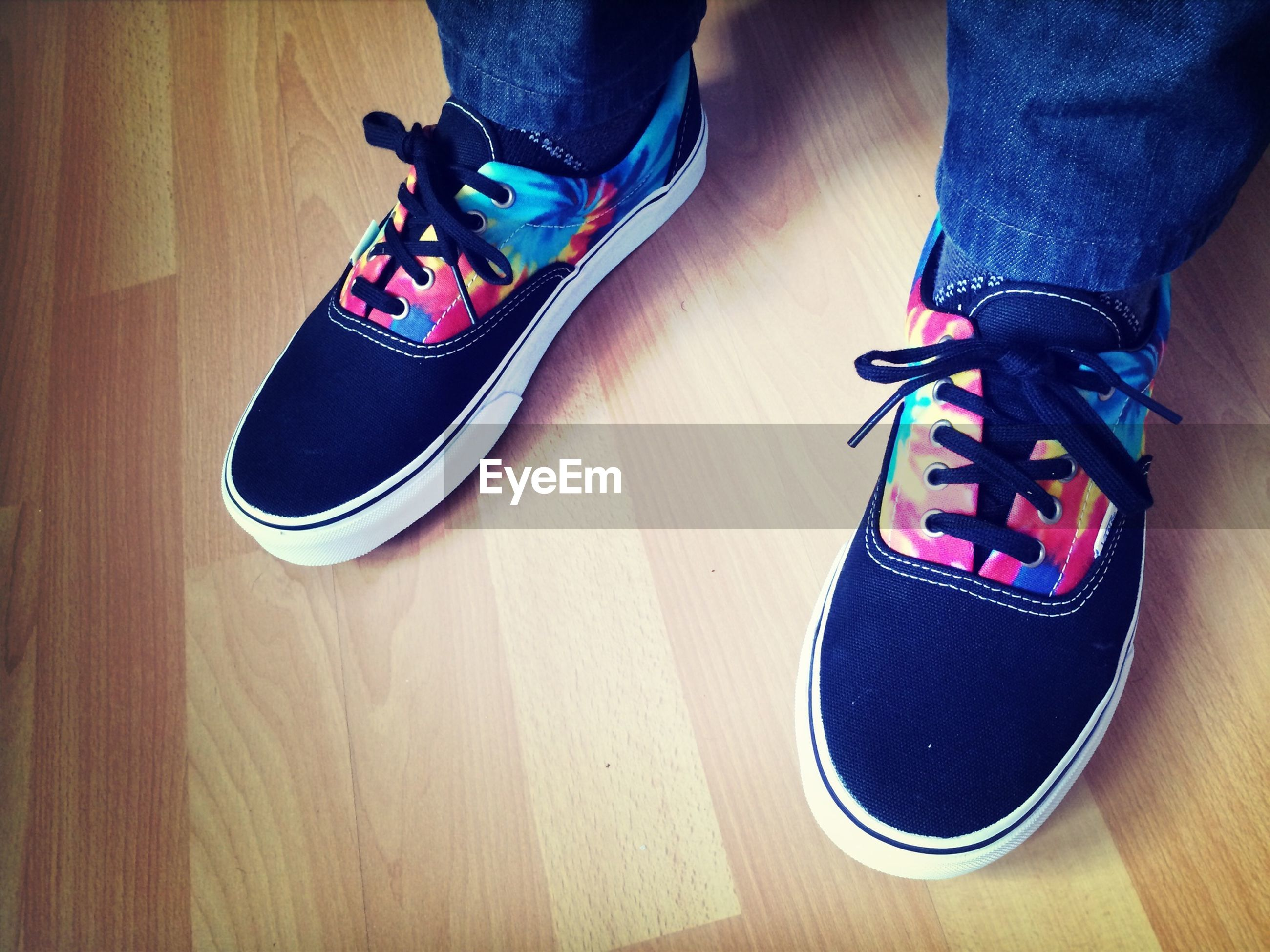 low section, indoors, person, shoe, footwear, lifestyles, high angle view, human foot, fashion, standing, jeans, leisure activity, men, casual clothing, sitting, canvas shoe