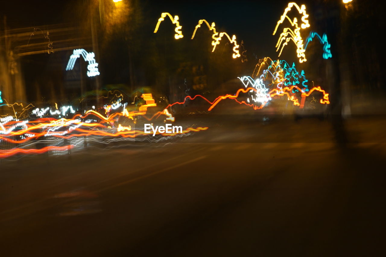 VIEW OF LIGHT TRAILS ON ROAD AT NIGHT