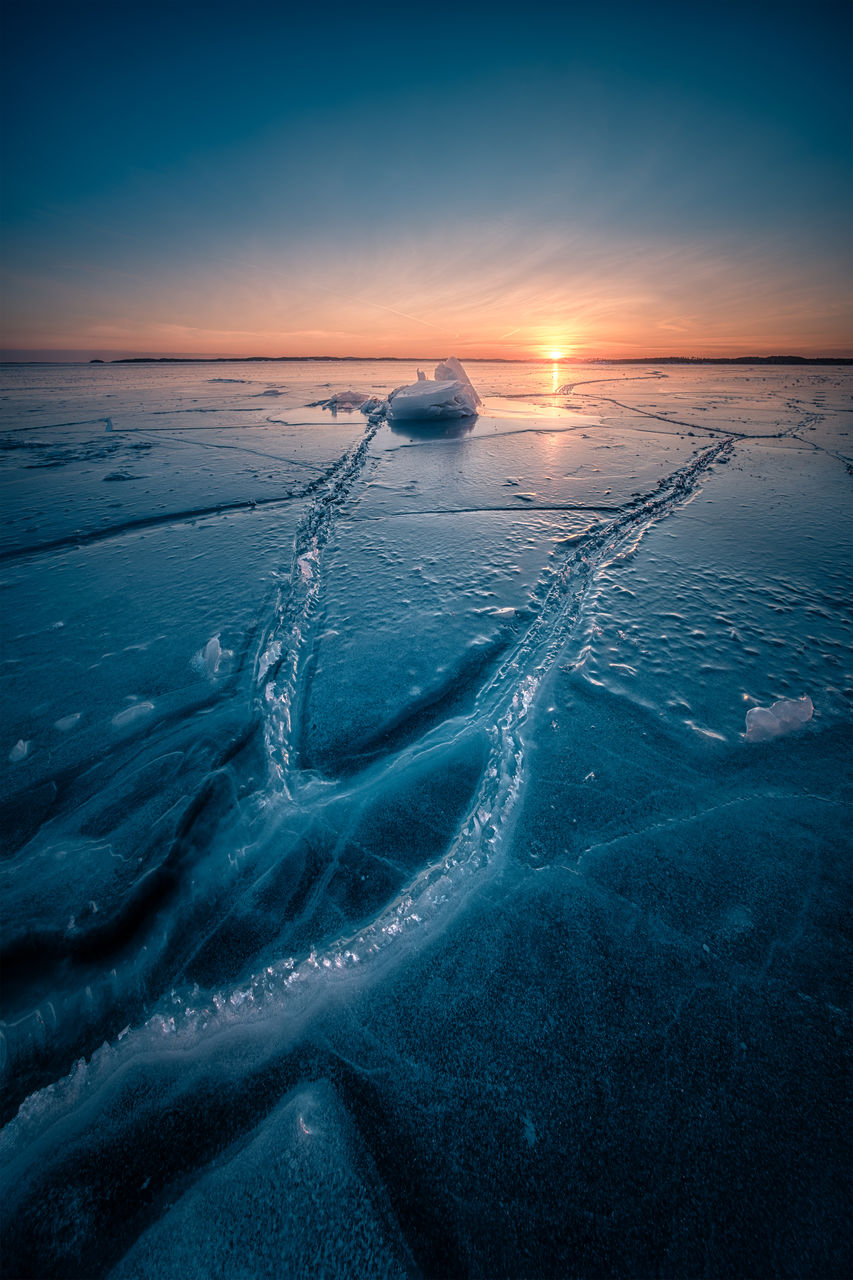 beauty in nature, sunset, nature, scenics, winter, cold temperature, outdoors, motion, tranquility, landscape, water, frozen, snow, no people, sea, sky, day
