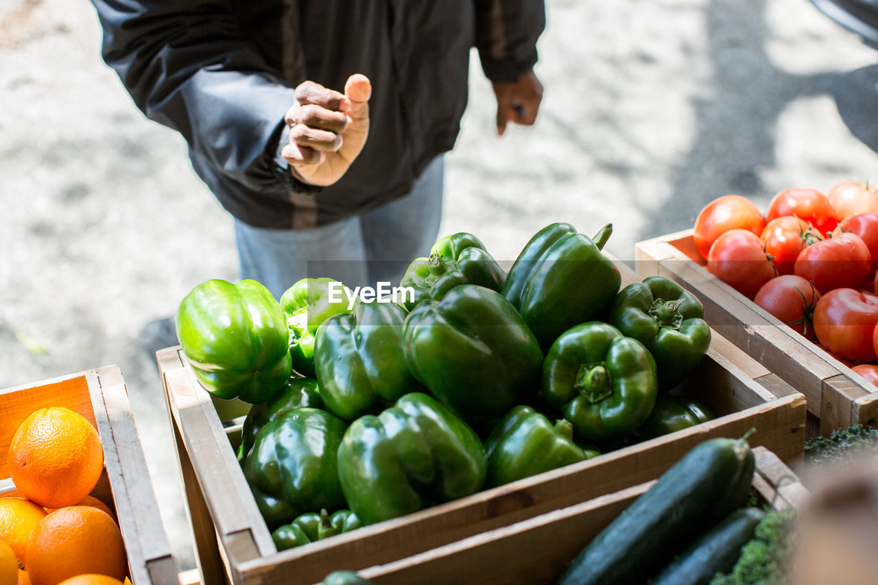 Midsection Of Man Standing At Vegetable Stall In Market