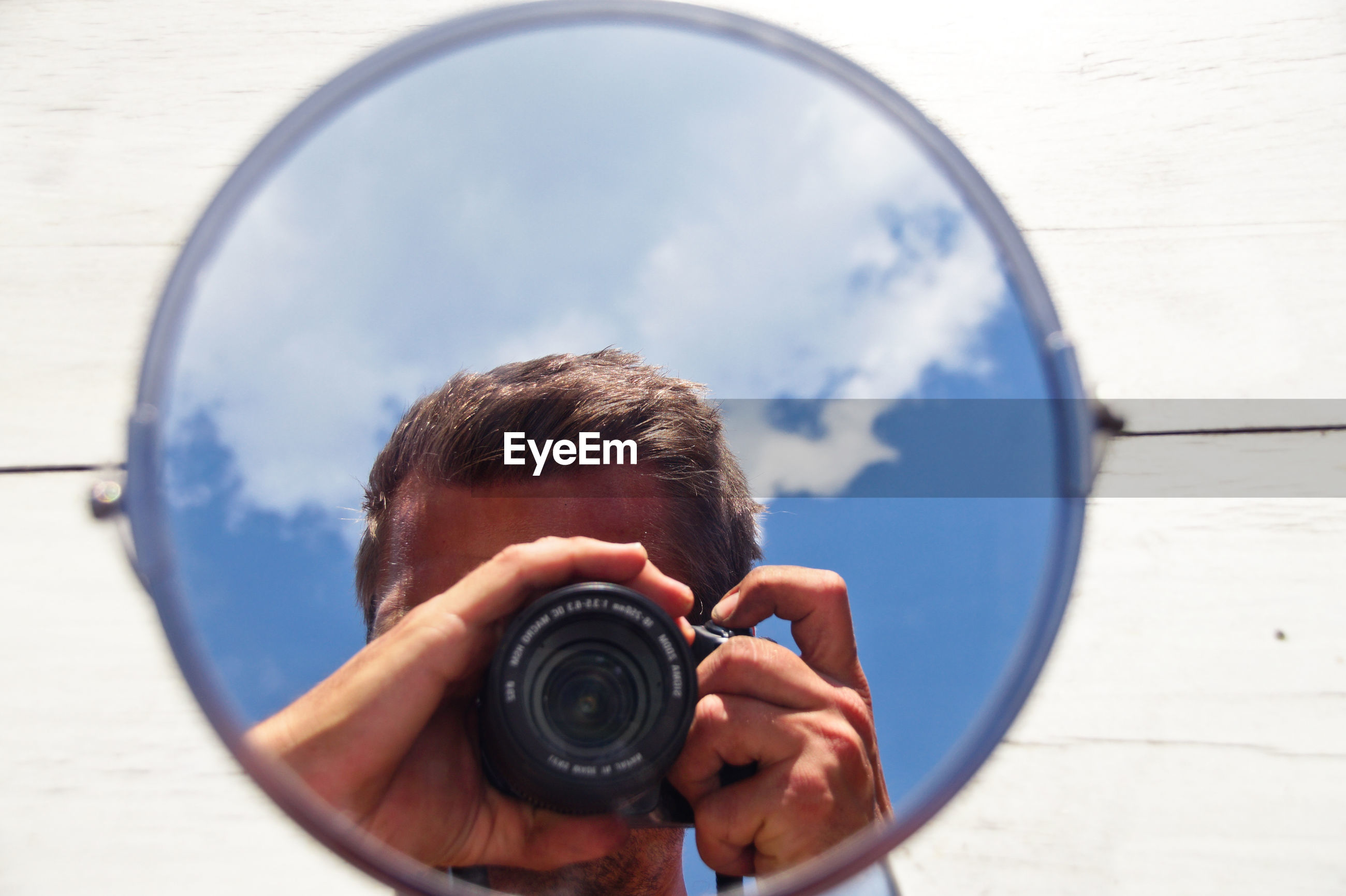 Reflection of man photographing through camera in mirror