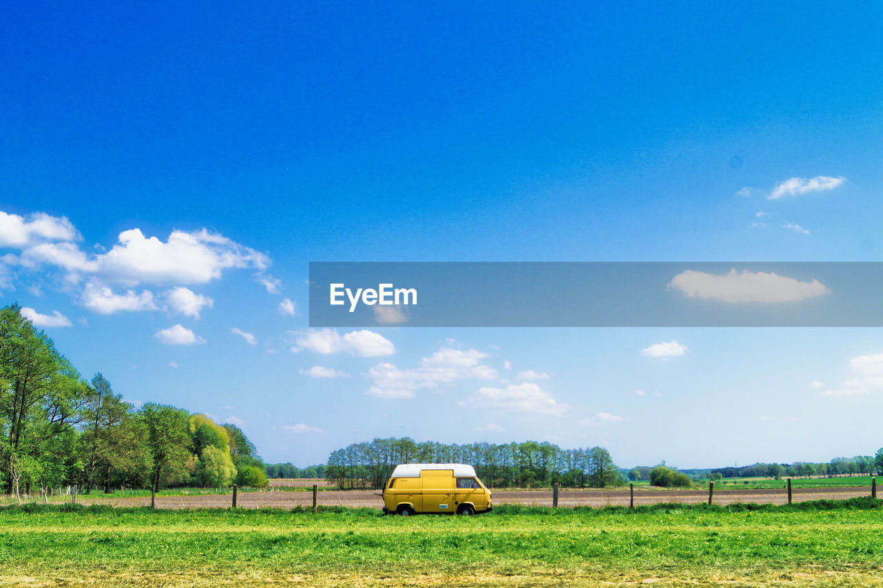 plant, field, land, sky, mode of transportation, tree, green color, nature, land vehicle, transportation, beauty in nature, grass, landscape, yellow, day, cloud - sky, no people, environment, car, sunlight, outdoors