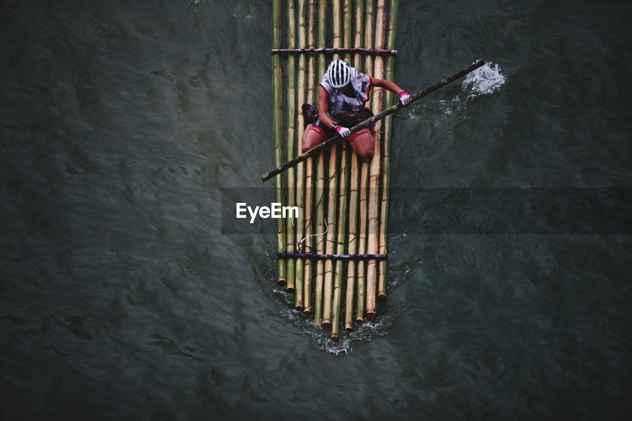 High angle view of man bamboo rafting on river
