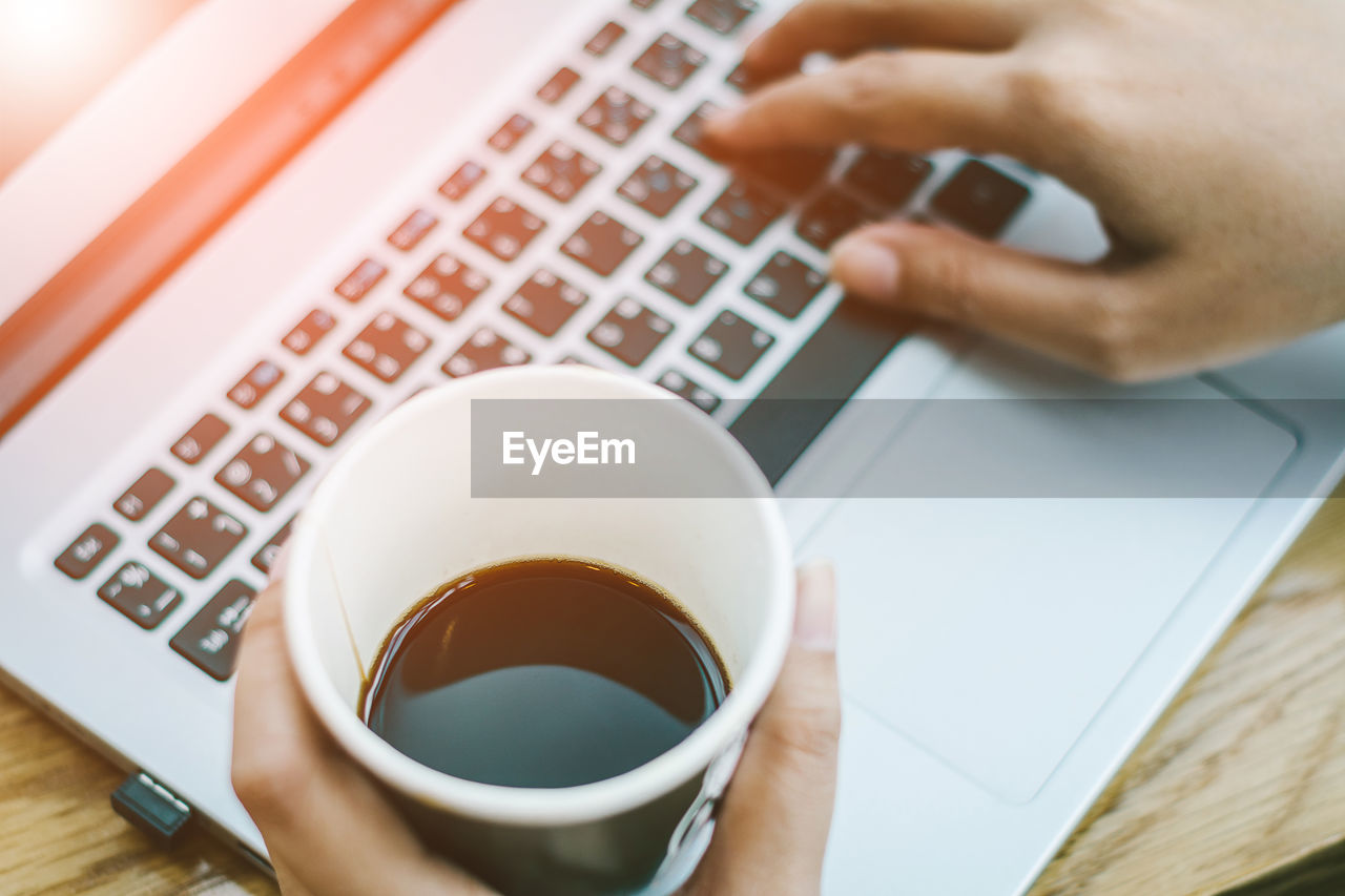 cup, drink, coffee, computer, mug, human hand, coffee - drink, one person, communication, technology, wireless technology, human body part, table, laptop, coffee cup, hand, real people, refreshment, connection, food and drink, keyboard, using laptop, finger