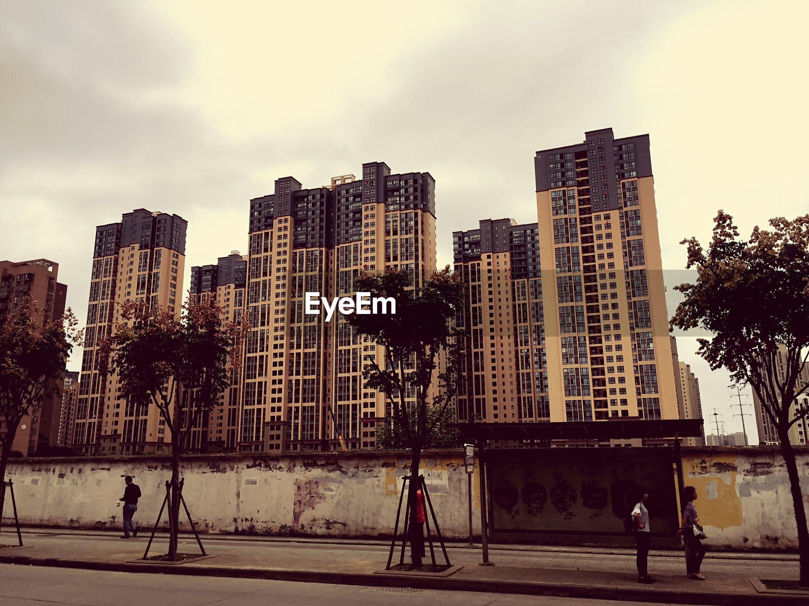 People walking on building against sky