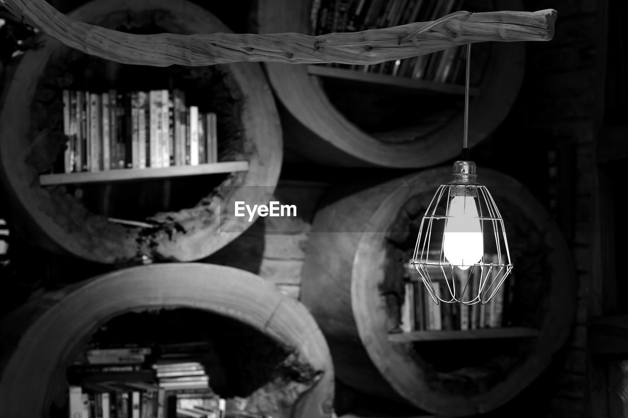 Close-Up Of Hanging Light Against Bookshelf