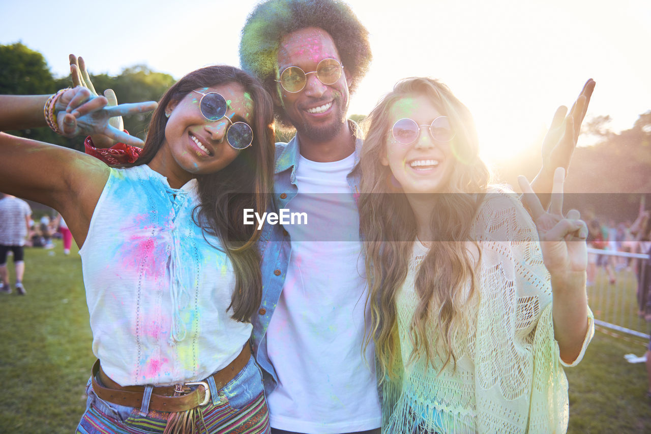 happiness, smiling, togetherness, emotion, fun, young adult, looking at camera, group of people, enjoyment, leisure activity, glasses, lifestyles, young women, portrait, festival, friendship, cheerful, sunglasses, real people, young men, fashion, positive emotion, music festival, holi, outdoors, human arm, lens flare