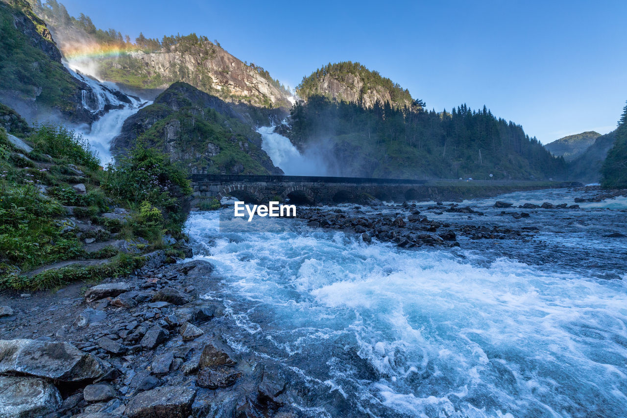 River Flowing Through Bridge With Mountains And Rainbow In The Distance