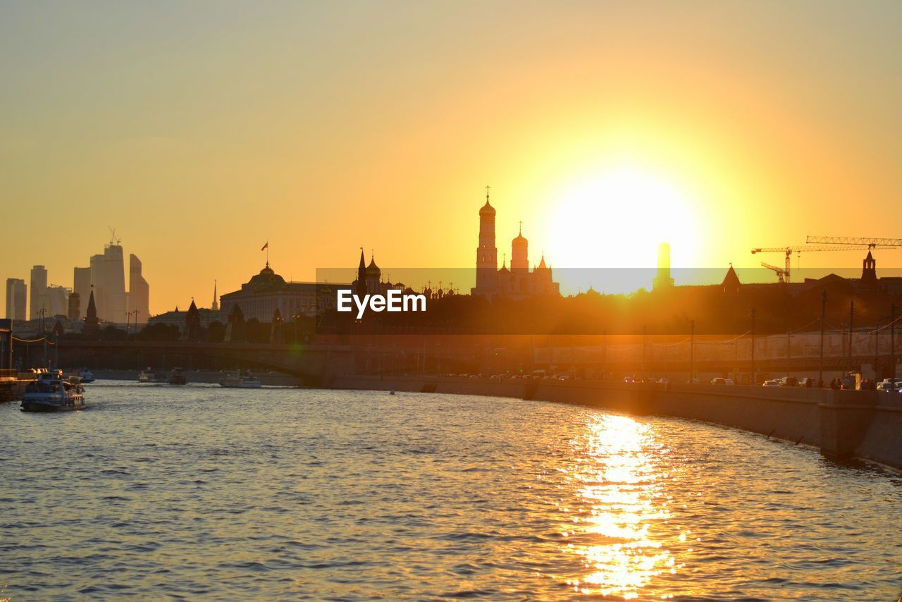 sunset, architecture, building exterior, built structure, water, sun, river, orange color, spirituality, travel destinations, sky, place of worship, transportation, waterfront, religion, lens flare, sunlight, city, sunbeam, nautical vessel, dome, tourism, outdoors, mode of transport, no people, travel, nature, gold colored, cityscape, clear sky, day