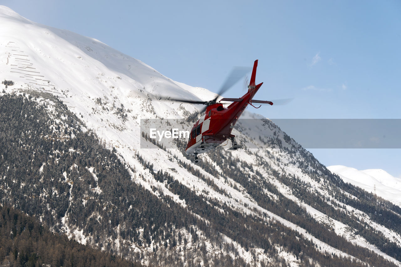Low Angle View Of Air Vehicle By Snowcapped Mountains Against Sky