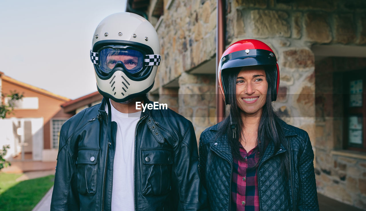 portrait, focus on foreground, front view, helmet, real people, looking at camera, lifestyles, standing, two people, waist up, clothing, smiling, people, headwear, leisure activity, emotion, young adult, togetherness, day, happiness, outdoors, teenager