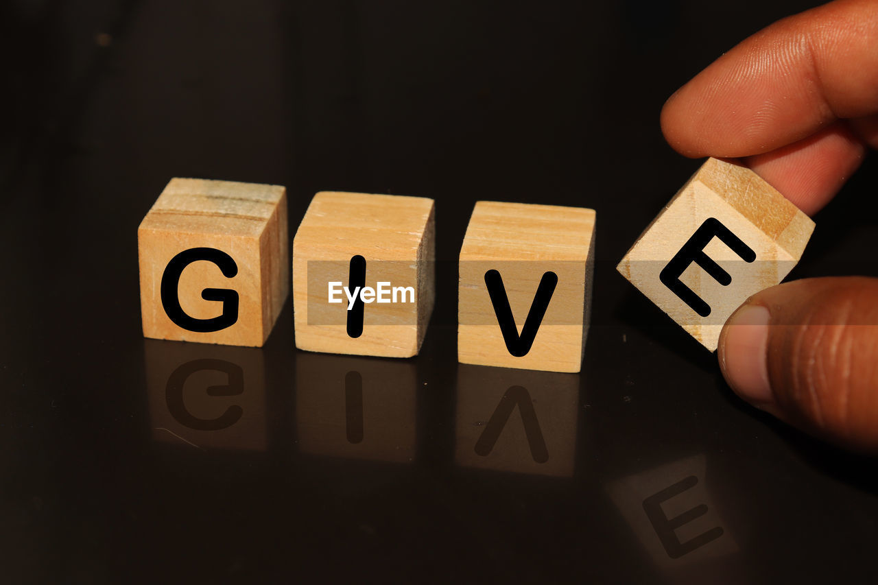 Cropped hand with give text on toy blocks against black background