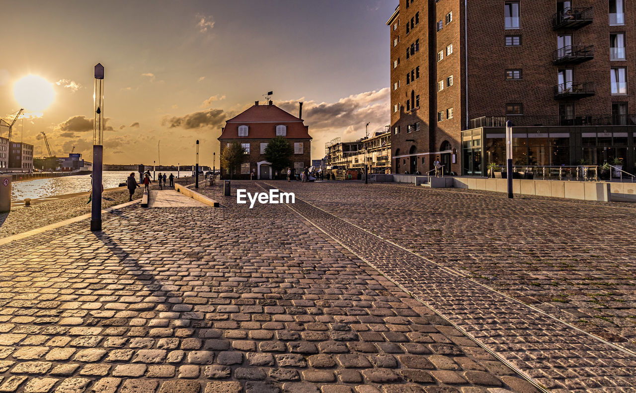 building exterior, street, architecture, built structure, city, sky, cobblestone, street light, lighting equipment, building, nature, footpath, illuminated, no people, the way forward, direction, outdoors, transportation, sunlight, empty, paving stone, light, long