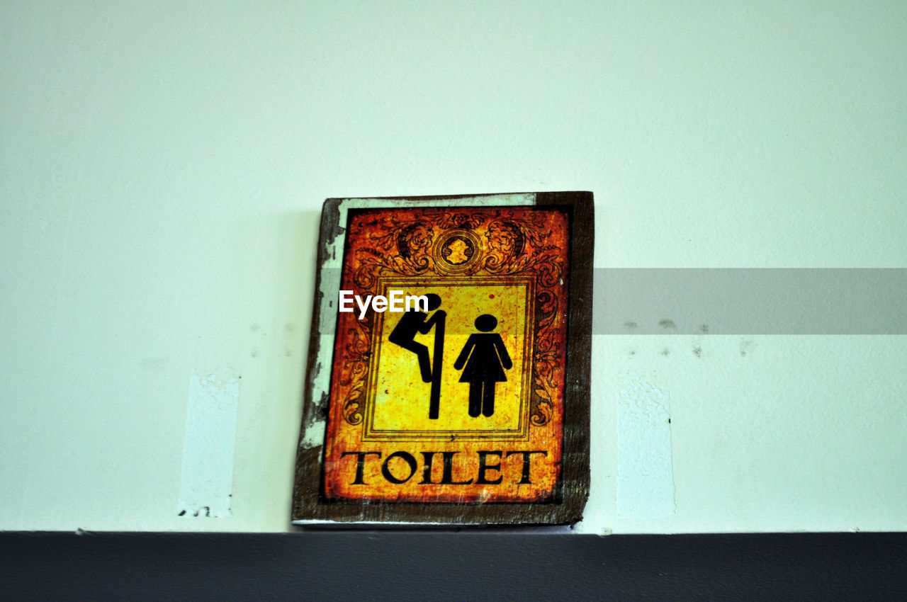 Low angle view of toilet sign on wall