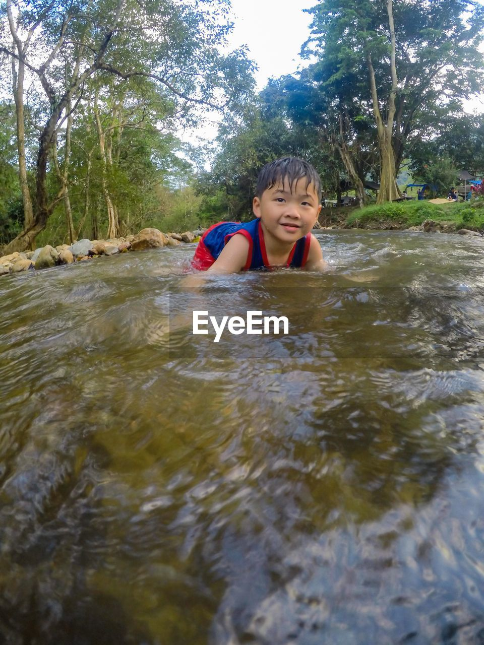 Smiling boy looking away while swimming in river against trees at forest
