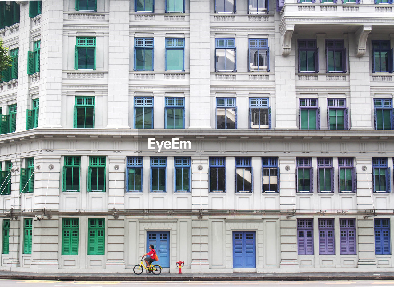 Man Riding Bicycle Against Buildings