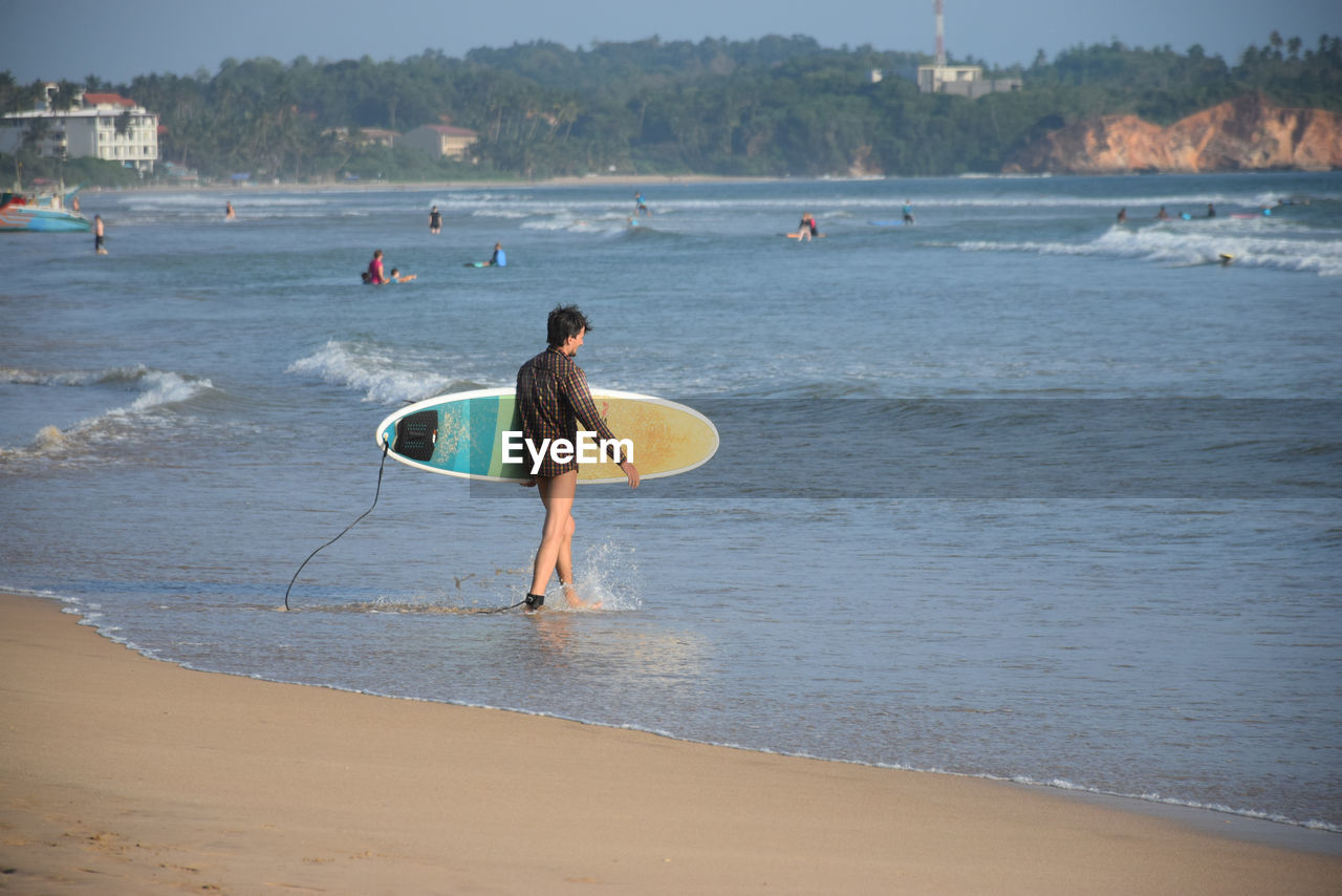 beach, sea, real people, surfboard, surfing, water, leisure activity, sport, enjoyment, sand, nature, one person, fun, skill, playing, outdoors, lifestyles, vacations, day, extreme sports, paddleboarding, men, wave, beauty in nature, people