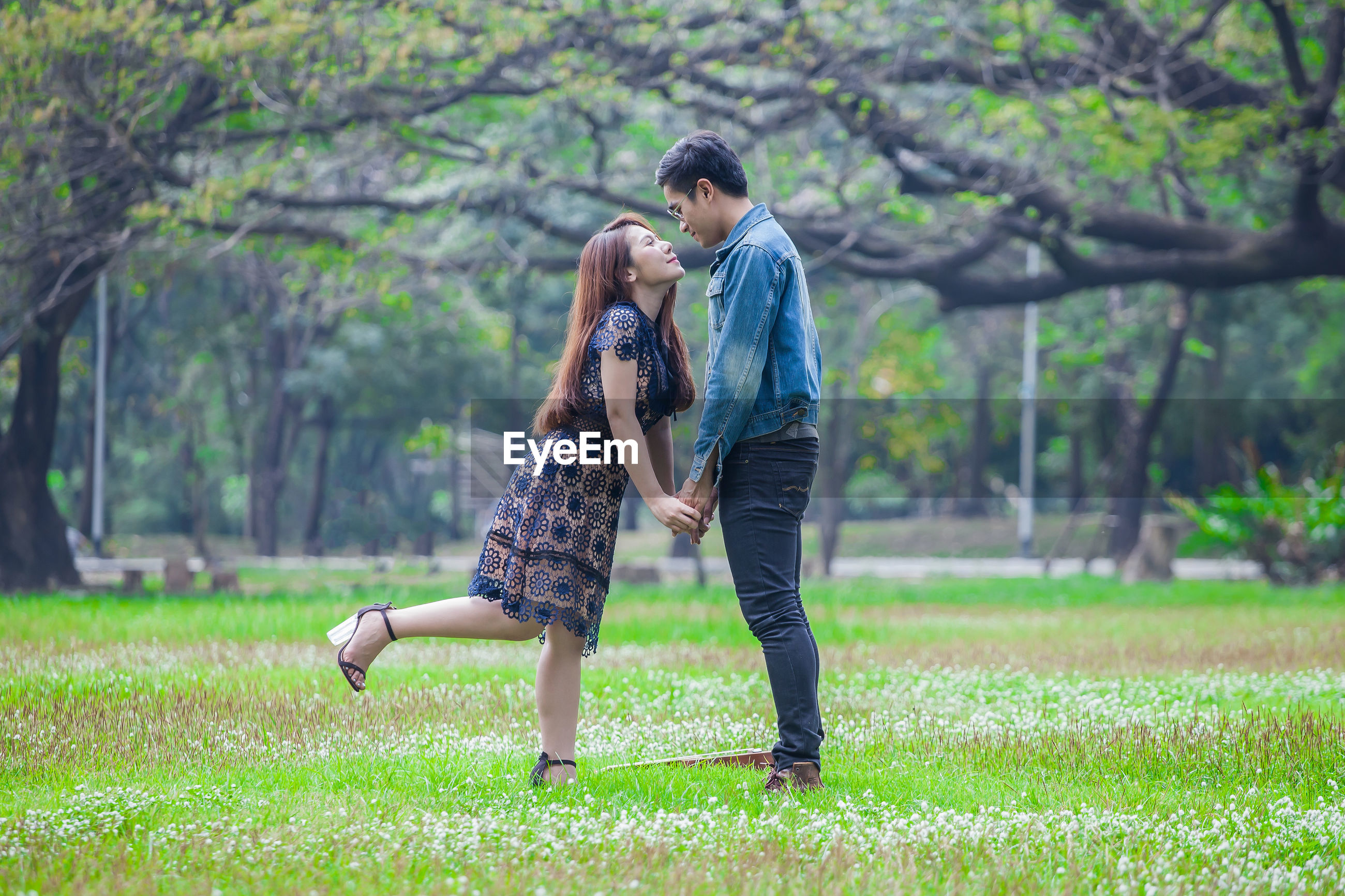 Couple face to face standing on field by trees