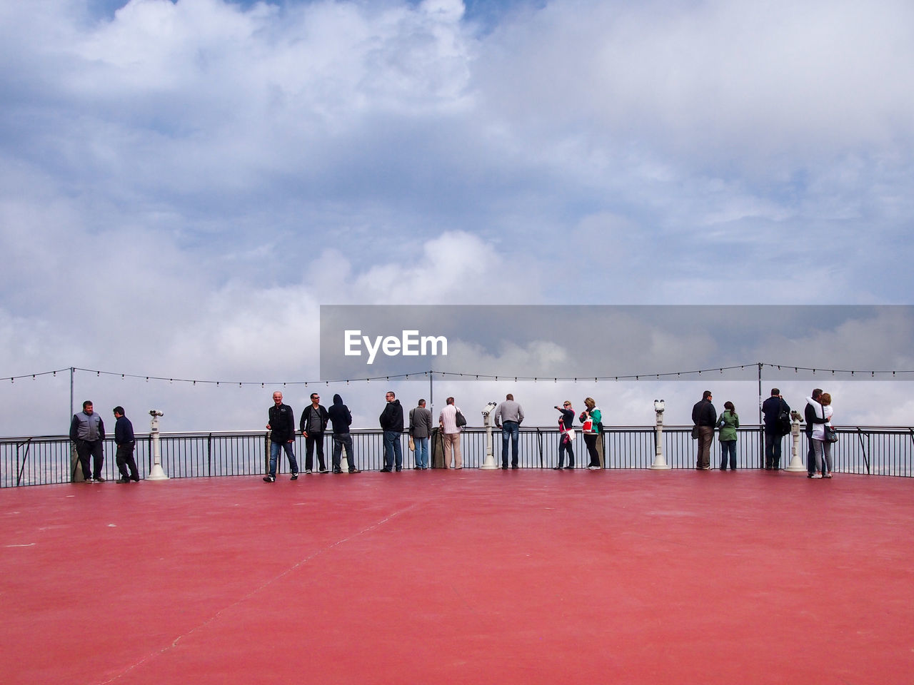 People At Observation Point Against Cloudy Sky