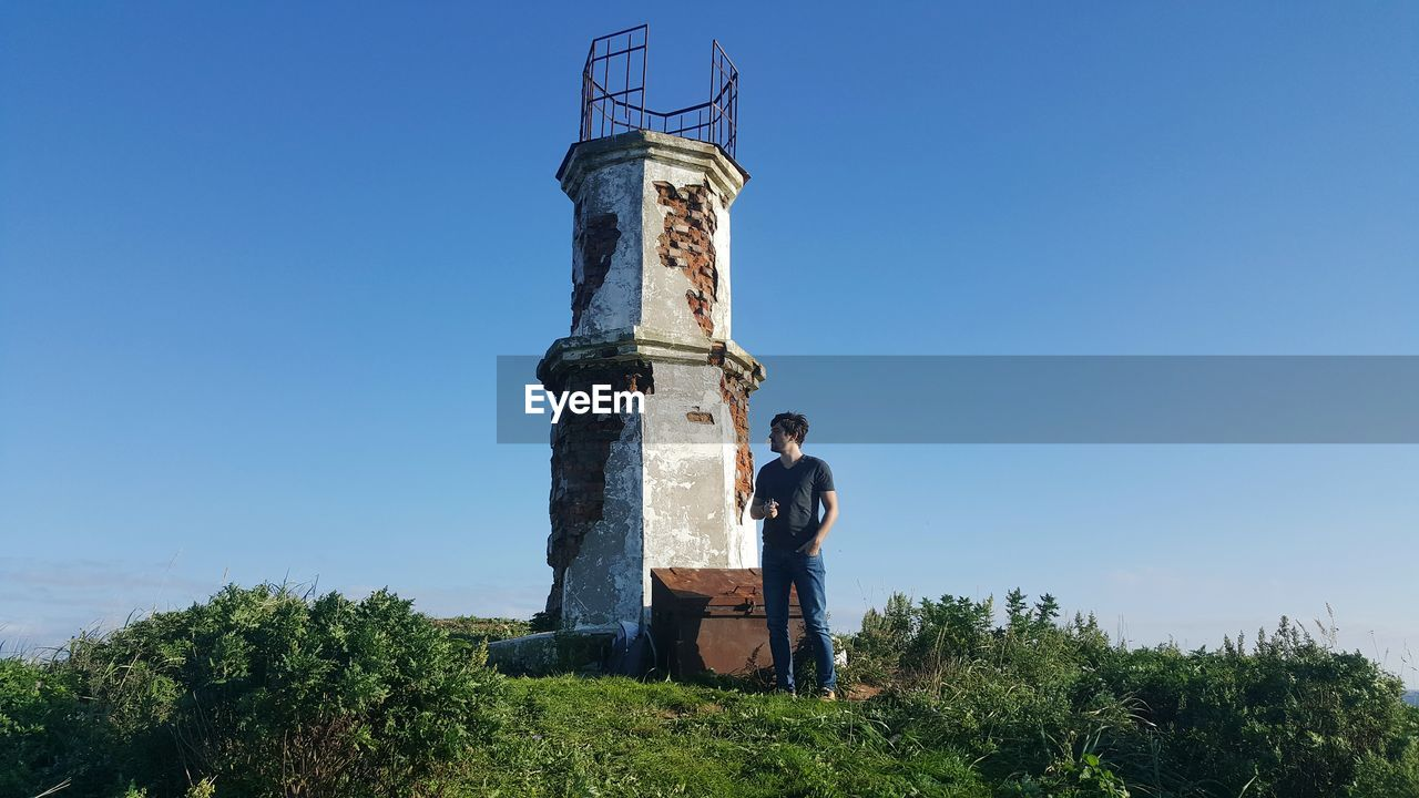 Man standing by abandoned lighthouse against blue sky