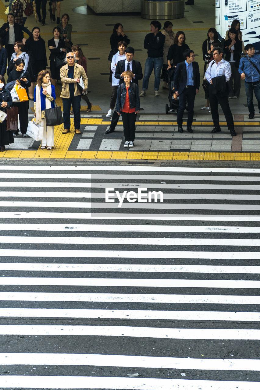 group of people, crosswalk, zebra crossing, city, road marking, crossing, crowd, large group of people, real people, architecture, walking, men, sign, women, street, transportation, marking, symbol, day, outdoors