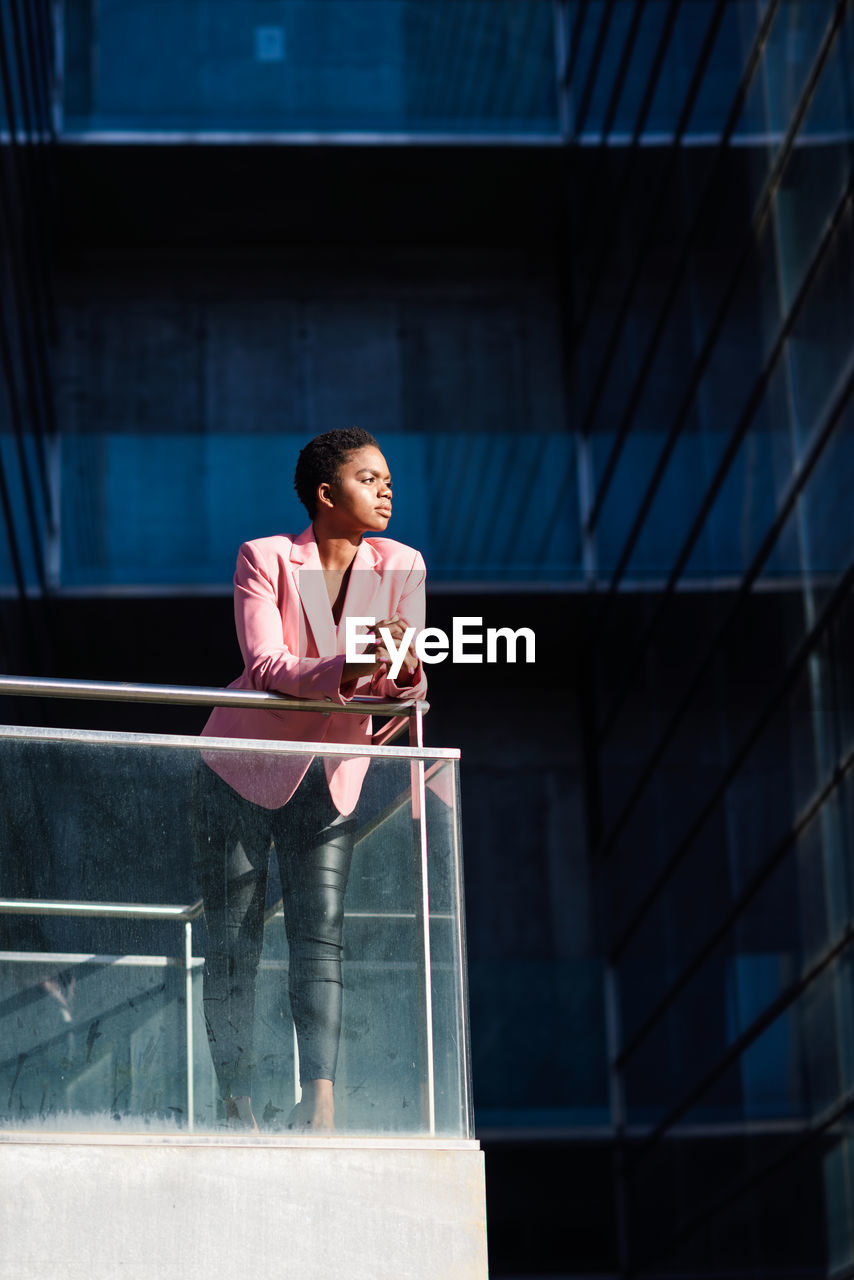 Businesswoman looking away while standing by railing in office