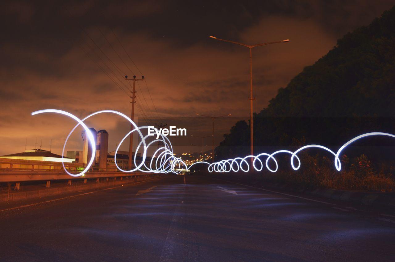 Illuminated light painting on road against sky at night